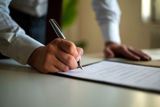 man signing estate planning document